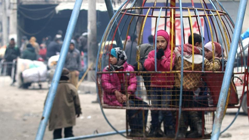 Children play while waiting to be evacuated with others from a rebel-held sector of eastern Aleppo, Syria.  (Abdalrehman Ismail/Reuters Photo)