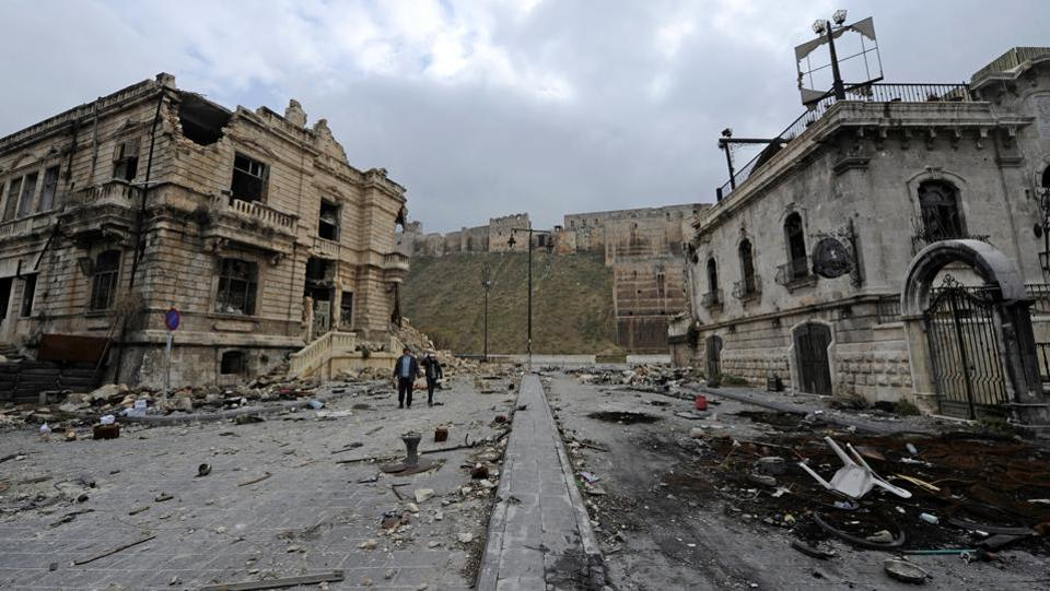 People walk past the old customs buildings (L) and Peoria restaurant (R) near Aleppo's historic citadel, in the government controlled area of the city. (Omar Sanadiki/Reuters Photo)