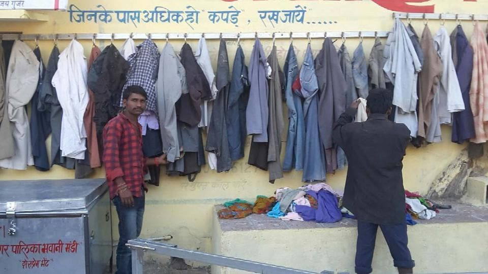 Two men check out garments left at the wall of kindness at Bhawanimandi in Jhalawar district on Sunday.