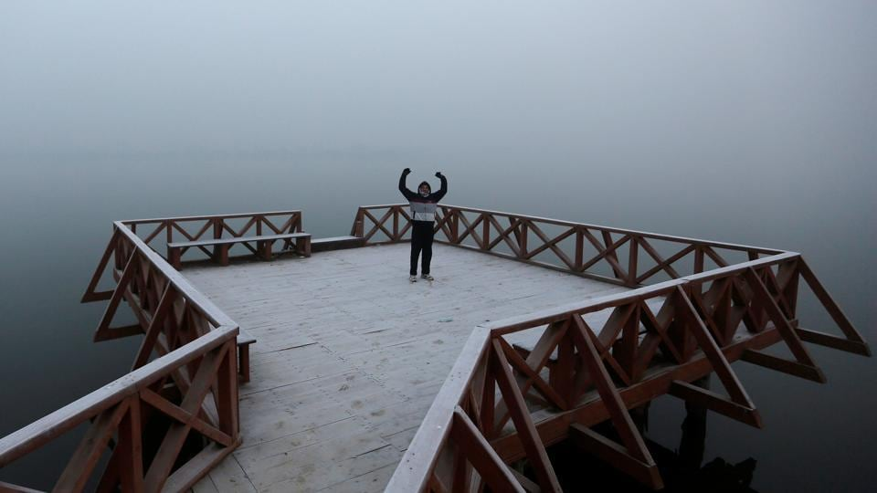 A man exercises on a jetty on the banks of Dal Lake on a cold winter morning in Srinagar.
