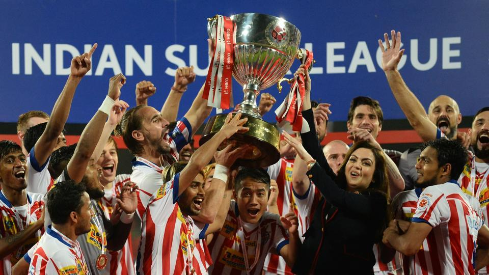 Atletico de Kolkata players celebrate with the trophy, presented by Indian Super League (ISL) director Nita Ambani (3rd R), after winning the ISL final football match against Kerala Blasters FC.