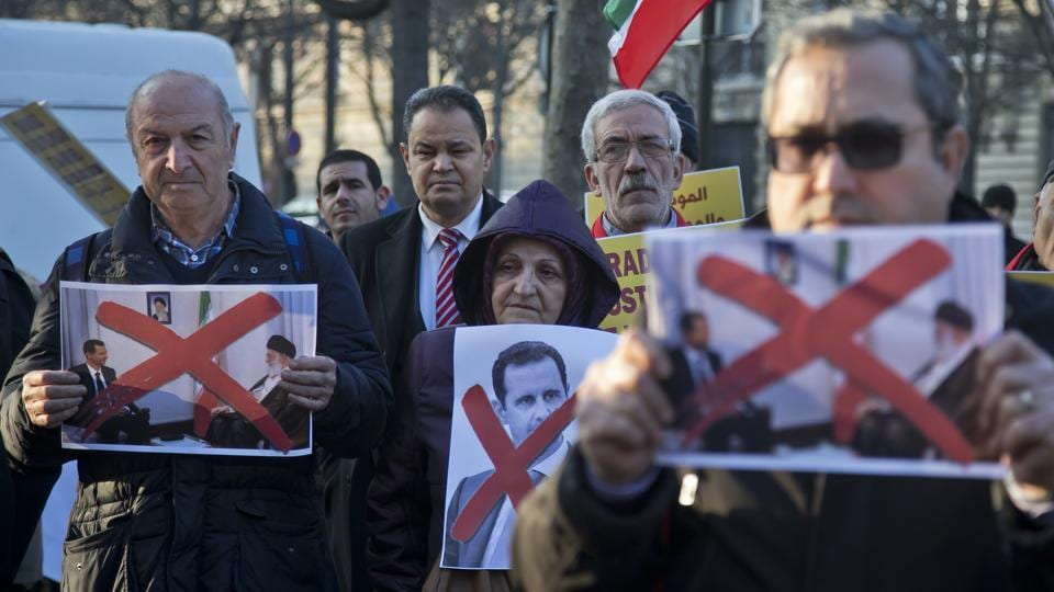Syrian and Iranian migrants hold pictures of Syrian President Bashar Assad and supreme leader Ayatollah Ali Khamenei during a gathering to protest against the war in Aleppo outside the Iranian embassy in Paris..  (Michel Euler/AP Photo)