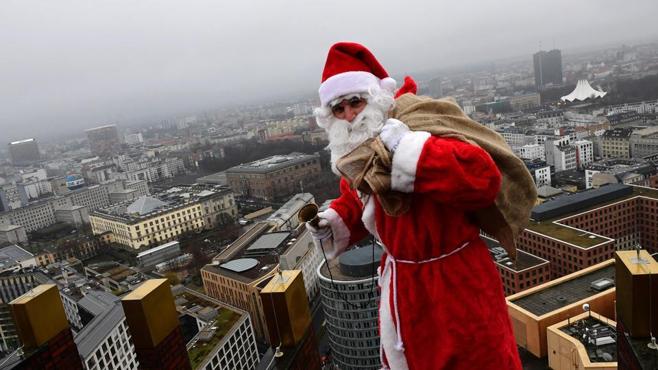 A man dressed as Father Christmas climbs the fascade next to the so-called