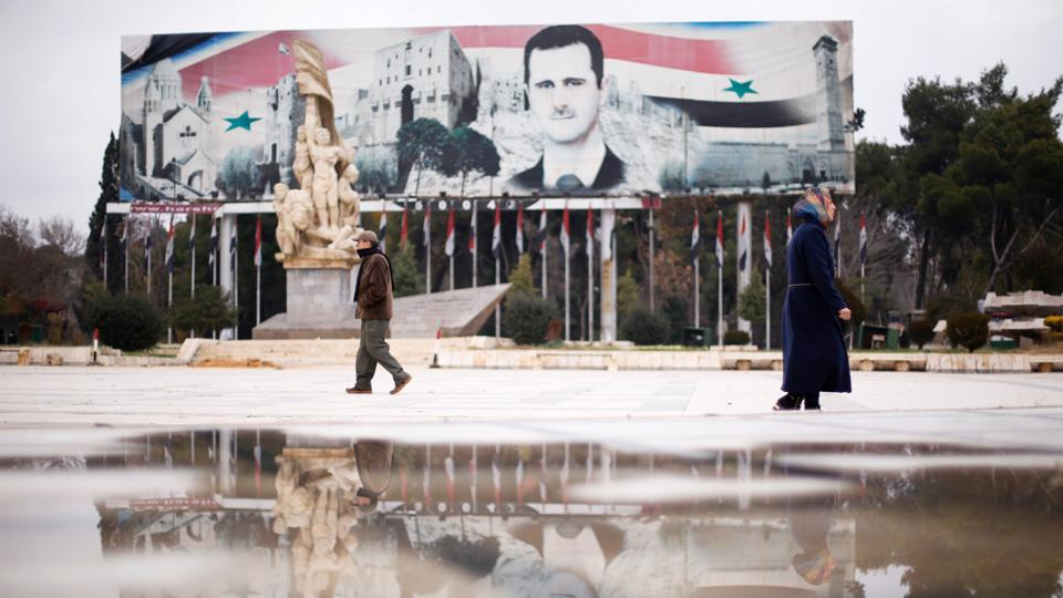 People walk past a billboard depicting Syria's President Bashar al-Assad at Saadallah al-Jabri Square, in the government controlled area of Aleppo, Syria. (Omar Sanadiki/Reuters Photo)
