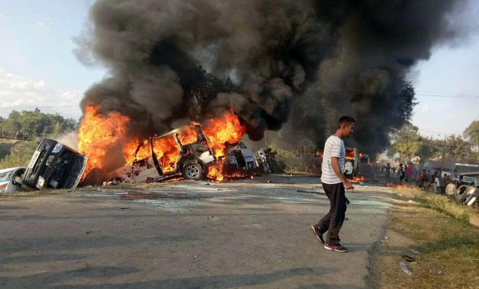 Vehicles are seen burning after being set alight by protesters in Imphal on Sunday.