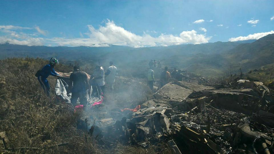 This handout picture released by sesarch and rescue team and available on December 18, 2016 shows Indonesian officials examining the Hercules military plane A-1334 that crashed in Wamena on December 18, 2016. Amilitary plane crashed on December 18 in remote mountainous region of Indonesia's Papua, killing 13 people on board, military and police officials said. / AFP PHOTO / SEARCH AND RESCUE TEAM / HANDOUT