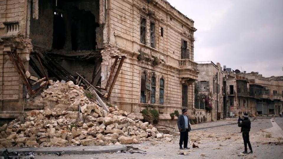 People take pictures in front of the old Customs building in the government controlled Old City of Aleppo, Syria.