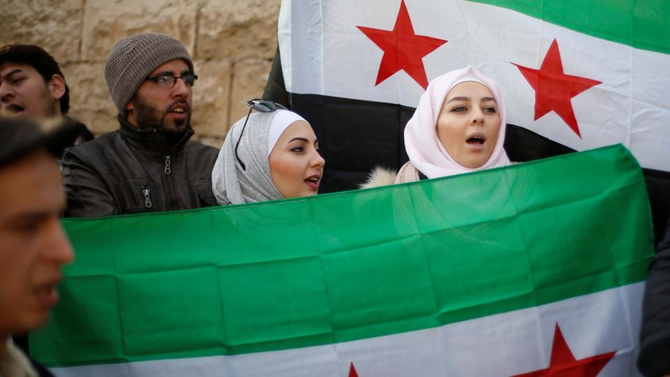 Protesters hold Syrian opposition flags and chant slogans during a sit-in, in solidarity with the people of Aleppo against the Syrian regime, in front of the UNDP office in Amman, Jordan.  (Muhammad Hamed/Reuters Photo)