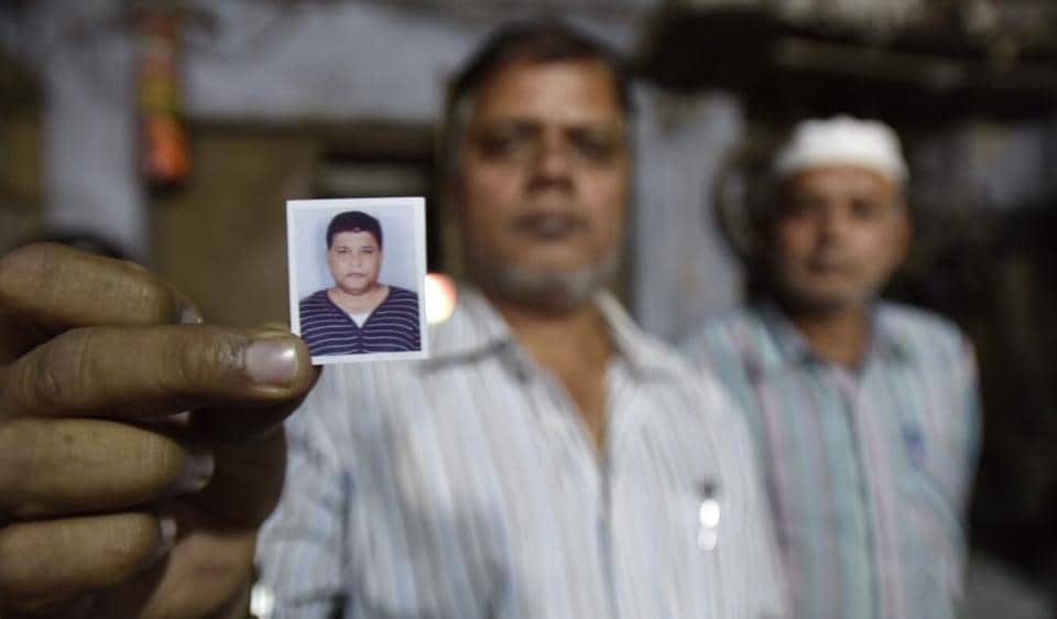 A relative shows a passport-size photo of Saur-ur-Rehman who died in a queue before a bank in Old Delhi area on November 16.