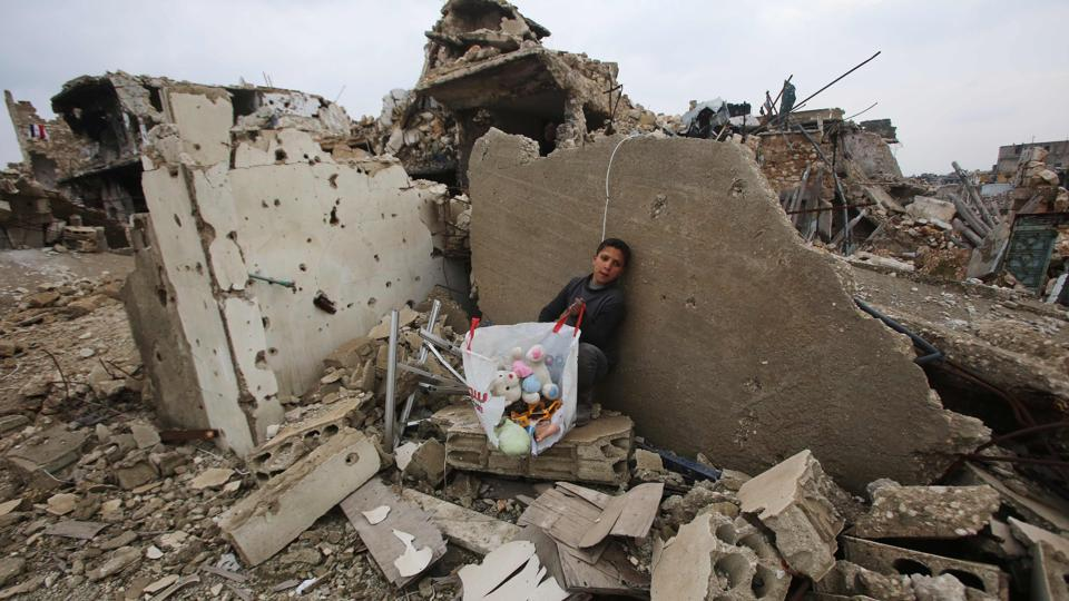 A Syrian boy sits with belongings he collected from the rubble of his house in Aleppo's Al-Arkoub neighbourhood after pro-government forces retook the area from rebel fighters.  (Youssef Karwashan/AFP Photo )