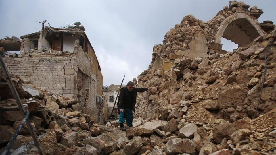 A Syrian man makes his way through the rubble of destroyed buildings as he heads to his house in Aleppo's Dahret Awad neighbourhood. (Youssef Karwashan/AFP Photo)