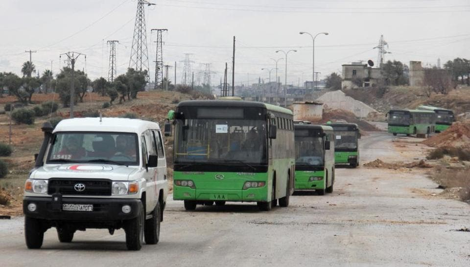 Buses sent to evacuate residents from Fuaa and Kafraya arrive at a rebel-held checkpoint on the outskirts of the two Syrian villages under rebel siege, on December 18.