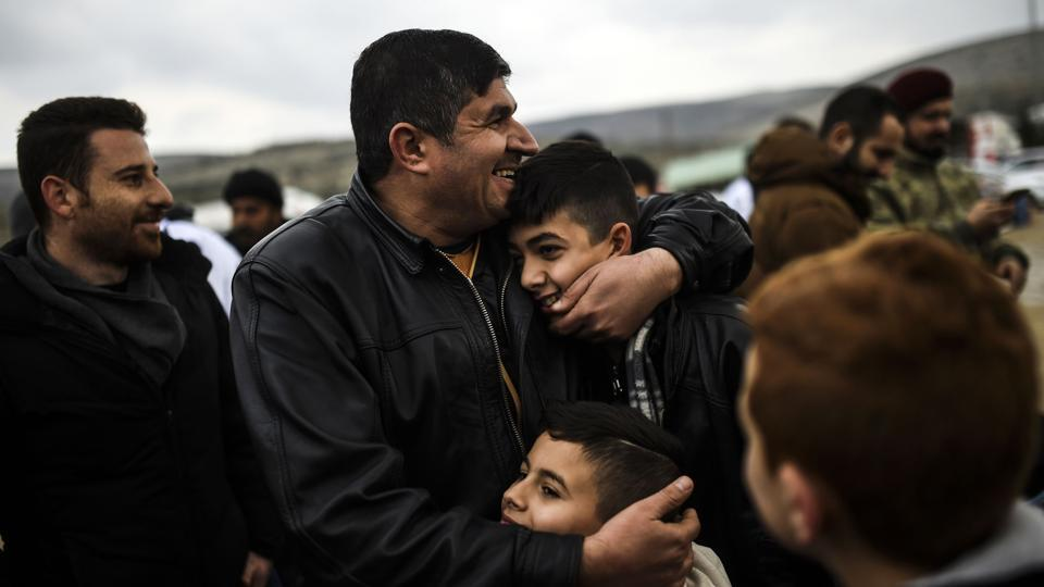 Syrian father Ali embraces his children upon their arrival from the Syrian city of Idlib to the Turkish crossing gate of Cilvegozu in Reyhanli in Hatay near the Syrian border. (Bulent Kilic/AFP Photo)