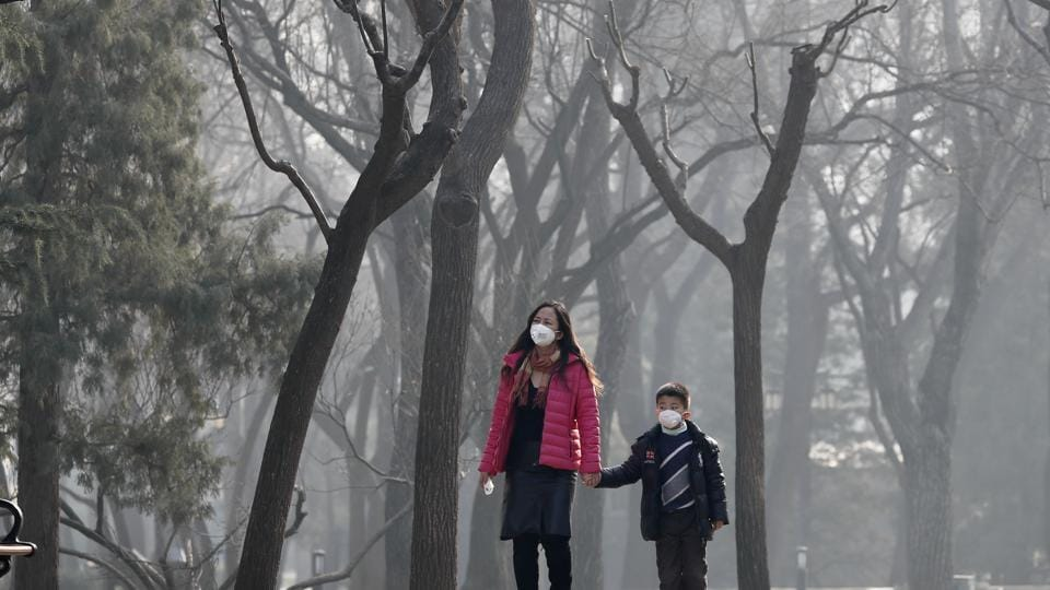 A woman and a child wear masks for protection against pollution at Ritan Park in Beijing on Monday.