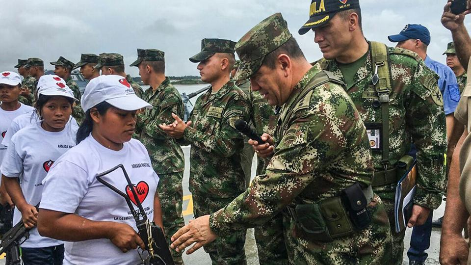 Members of the ELN guerrilla, who demobilised, hand over their weapons to the commander of Colombia's Armed Forces.