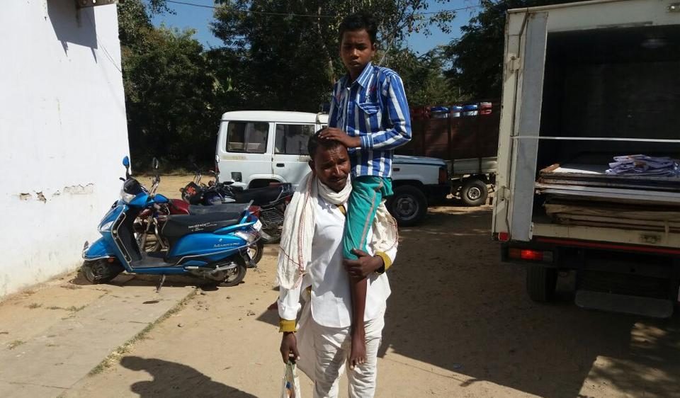 Deviram carries his son on his shoulder in Betul district.