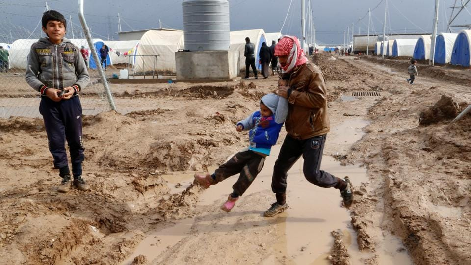 Displaced Iraqis who fled the Islamic State stronghold of Mosul, walk in the mud following heavy rain at Khazer camp, Iraq, December 19, 2016.  (Ammar Awad / REUTERS)