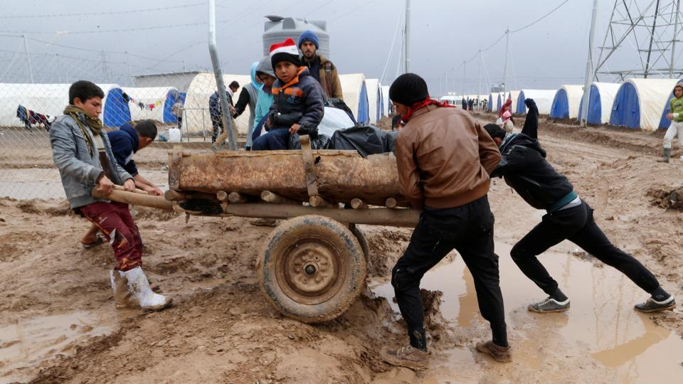 Displaced Iraqis who fled the Islamic State stronghold of Mosul, push a cart through mud following heavy rain at the Khazer camp, Iraq.  (Ammar Awad / REUTERS)