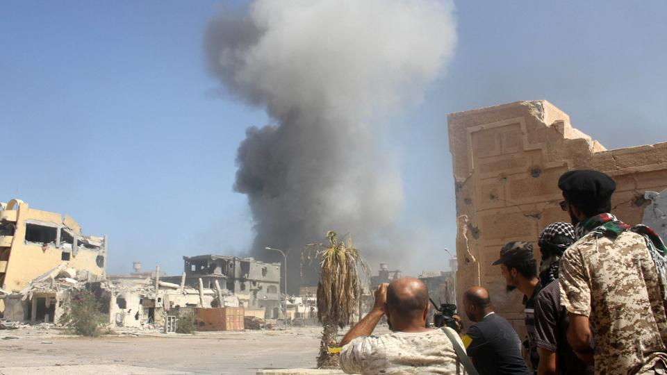 Smoke rises as Libyan forces allied with the UN-backed government take cover during a battle with Islamic State militants.