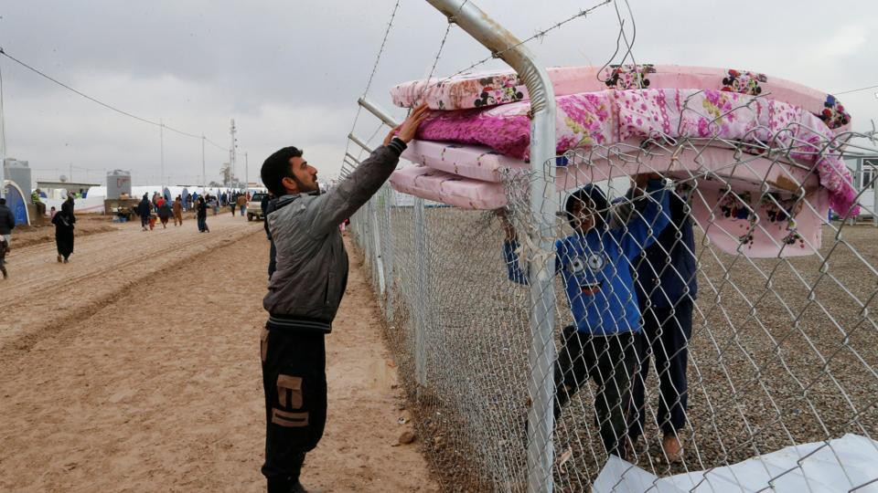 An Iraqi man who fled from Mosul, receives bedding at the Khazer camp in Iraq.  (Ammar Awad / REUTERS)