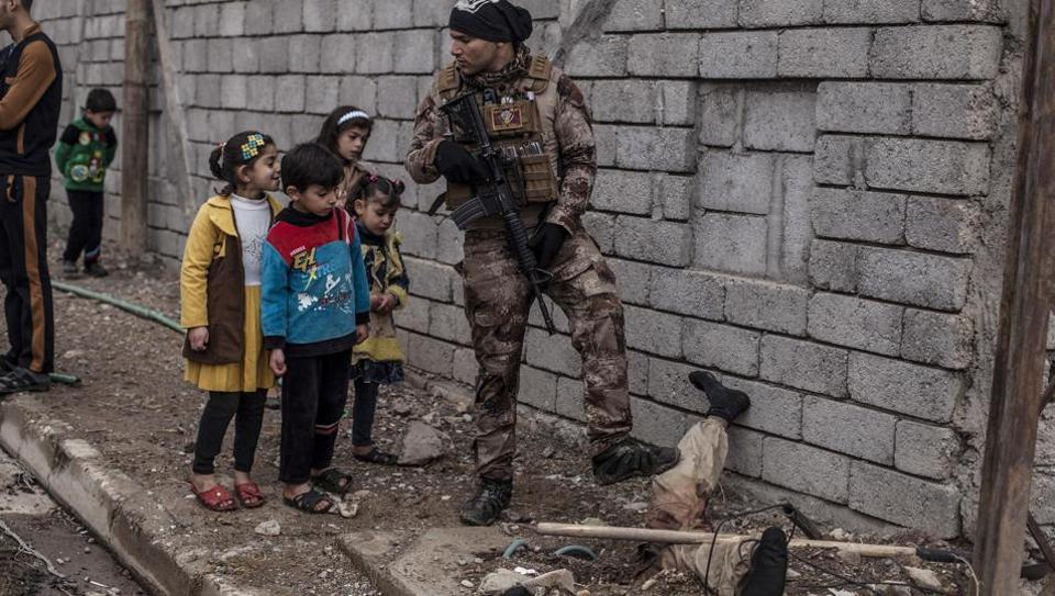 Iraqi children look at the body of a half-buried Islamic State militant while talking to an Iraqi soldier in the al-Barid district in Mosul, Iraq. In a part of Mosul that had been reclaimed from the Islamic State group (IS) days ago, Iraqi special forces were attacked on Sunday by drones operated by IS fighters inside the city. (Manu Brabo / AP)