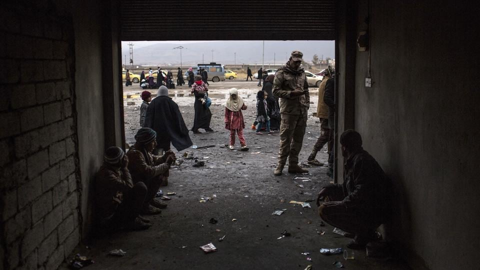 An Iraqi girl plays while waiting to be transferred to a camp with her family from a gathering point near Mosul. Hundreds of Iraqis were waiting to undergo a screening by the military  before getting sent to displaced -people  camps.  (Manu Brabo / AP)