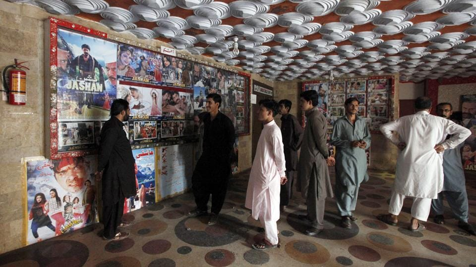 Pakistani cinema-goers look at photos displayed at a hall in Karachi on December 18, 2016. A Pakistan Film Exhibitors Association official said cinema owners had decided to resume screening Indian movies after a two-month self-imposed ban.