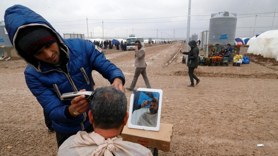 A man gets a haircut at Khazer camp, Iraq. Many of the displaced anticipate that their stay at the camp may be prolonged if the fight against Islamic State rages on.   (Ammar Awad / REUTERS)