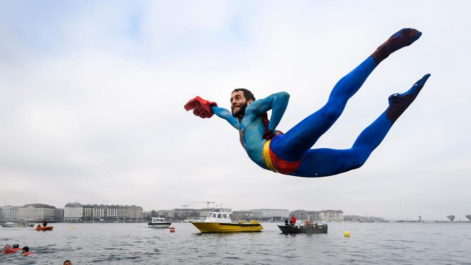 A swimmer disguised as Superman dives into the lake during the 78th