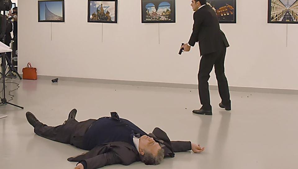 This picture taken on December 19 shows Andrey Karlov (L), the Russian ambassador to Ankara, lying on the floor after being shot by a gunman (R) during an attack during a public event in Ankara.