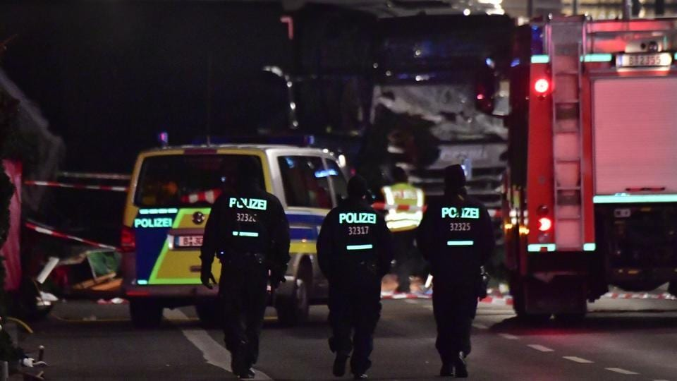 Police walk before the truck that had sped into a Christmas market in Berlin, on Monday, killing twelve people and injuring dozens more.