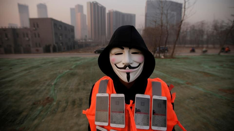 Artist Liu Bolin wears a mask and a vest with mobile phones as he live broadcasts air pollution in Beijing. (Reuters photo)