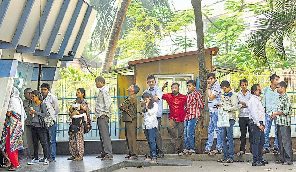 People queue outside an ATM at Antop Hill on Tuesday.