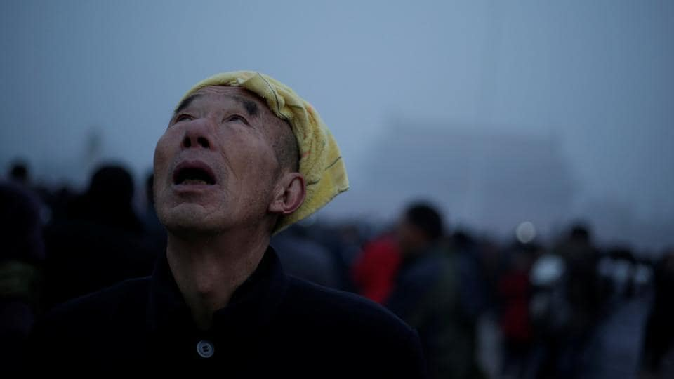 A tourist waits for a flag-raising ceremony at Tiananmen Square amid heavy air pollution in Beijing. (Reuters photo)