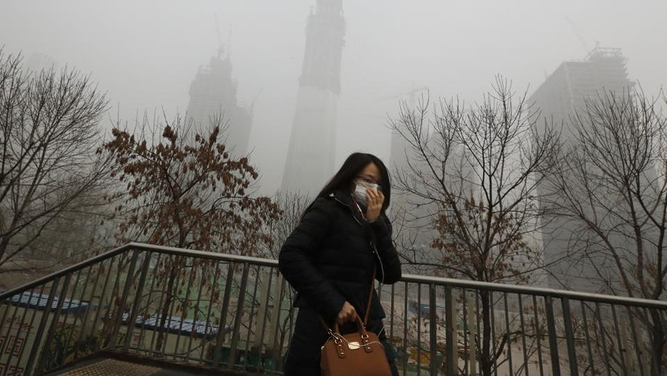 A woman holds her mask to protect herself from air pollution in Beijing. Authorities have shut down schools, ordered thousands of vehicles to go off roads and asked residents to stay indoors. (AP photo)