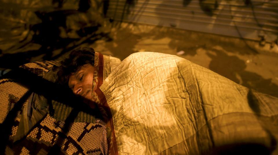 A man sleeps on  a footpath near Byculla station in Mumbai. (Pratik Chorge/HT PHOTO)