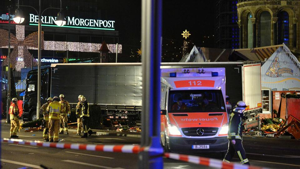 Police anbd firefighters work around the truck that crashed into a Christmas market at Gedächniskirche church in Berlin.