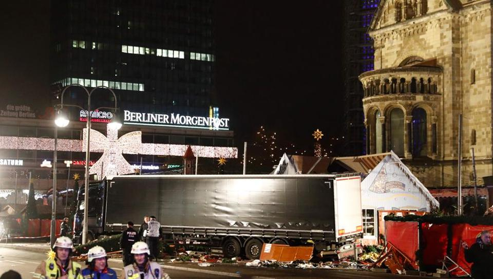 Police and firefighters work around the truck that crashed into a Christmas market at Gedächniskirche church in Berlin.