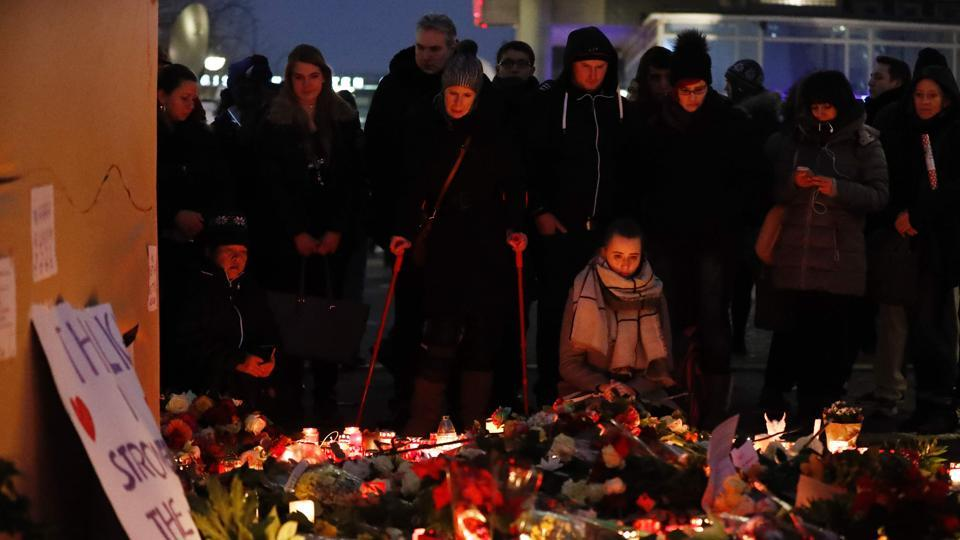 People stand on December 20, 2016 at a makeshift memorial in front of the Kaiser-Wilhelm-Gedaechtniskirche (Kaiser Wilhelm Memorial Church) in Berlin, where a truck crashed the day before into a Christmas market. Twelve people were killed and almost 50 wounded, 18 seriously, when the lorry tore through the crowd on December 19, 2016.