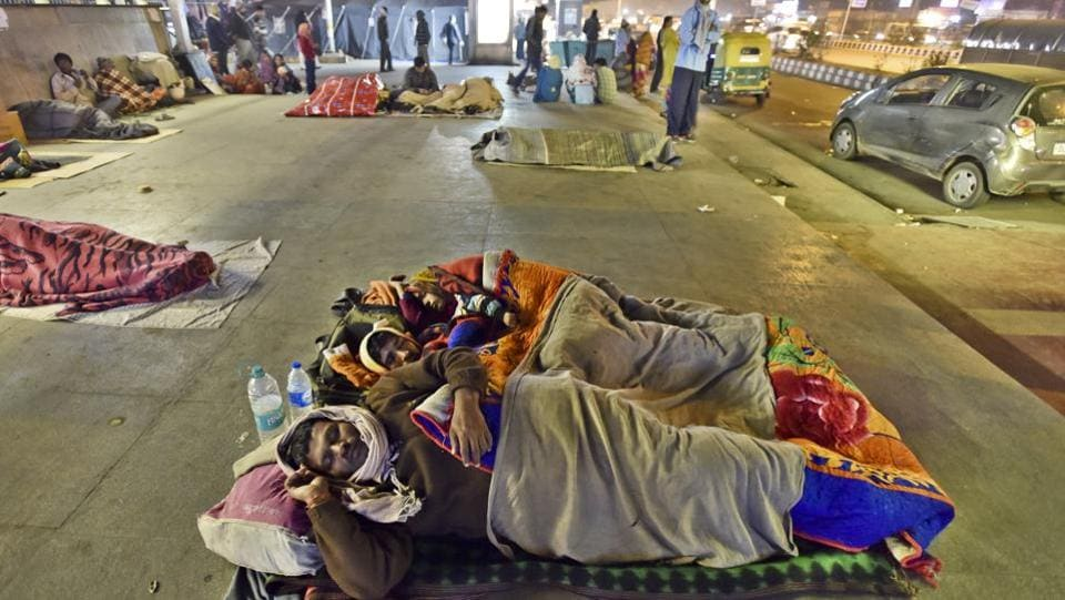 People sleep on a pavement outside the All India Institute of Medical Sciences (AIIMS).  The Delhi Urban Shelter Improvement Board (DUSIB) says it has 92 permanent shelters and 112 porta cabins that are operational throughout the year, but these often do not accommodate or are not preferred by the bulk of homeless that come to the city each year. (Sanjeev Verma/HT PHOTO)