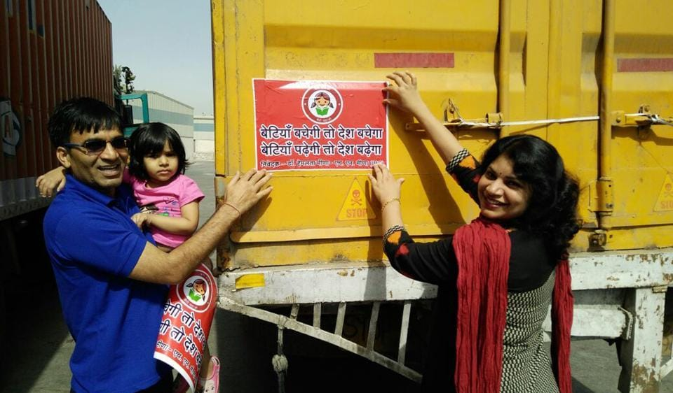 HN Meena and his wife Prof Hemlata Meena put stickers on a truck as part of their campaign in Neemuch.