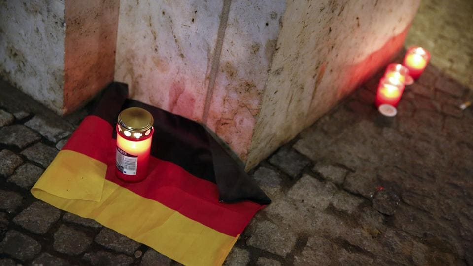 A candle is burning on a German national flag near the site where a truck ploughed through a crowd at a Berlin Christmas market on Breitscheidplatz square near the fashionable Kurfuerstendamm avenue in the west of Berlin, Germany, December 20, 2016