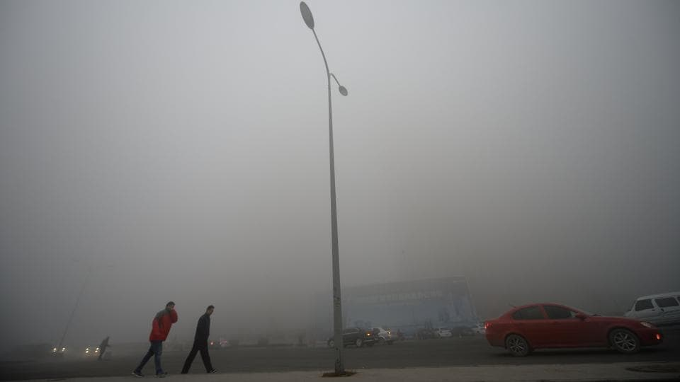 People walk in heavy smog during a polluted day in Jinan, Shandong province. (Reuters photo)