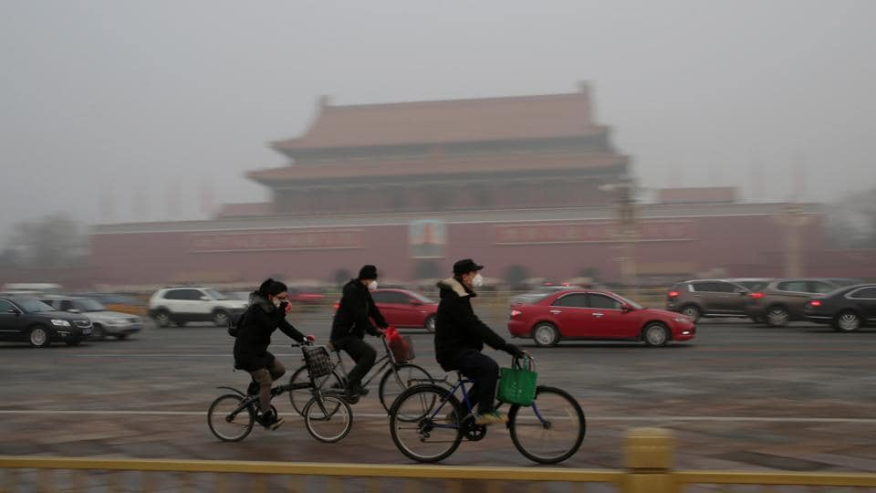 People cycle past Tiananmen Gate in Beijing. (Reuters photo)