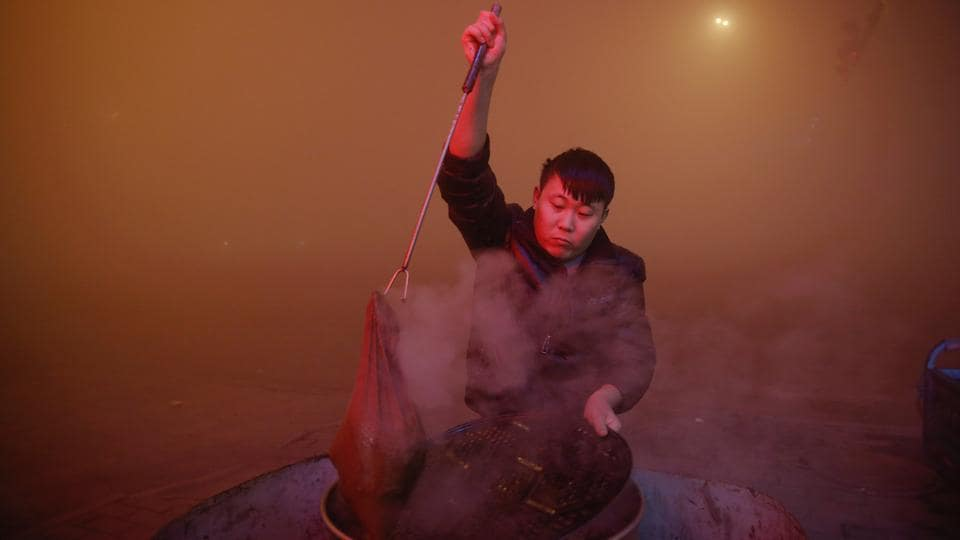 A man cooks in open air as heavy smog blankets Shengfang in Hebei province. (Reuters photo)