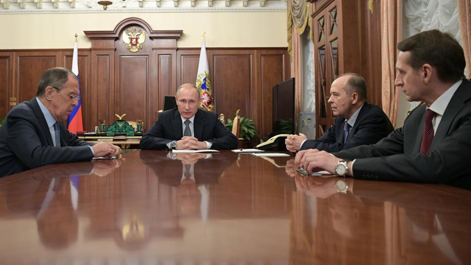 Russian President Vladimir Putin (2nd L) speaks with foreign minister Sergei Lavrov (L), director of the Foreign Intelligence Service (SVR) Sergei Naryshkin (R) and Alexander Bortnikov (2nd R), director of the Federal Security Service (FSB), during a meeting at the Kremlin in Moscow on December 19.