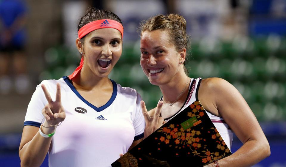 Sania Mirza (L) and Barbora Strycova of Czech Republic pose with their Pan Pacific Open Women's Doubles trophy.
