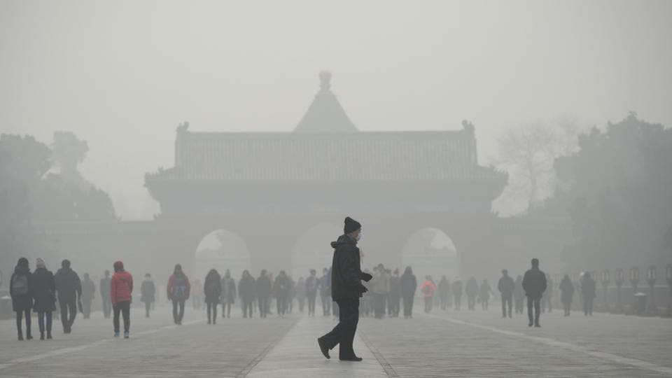 An elderly man in front of the Temple of Heaven park in Beijing, which is engulfed in heavy smog, on Tuesday.