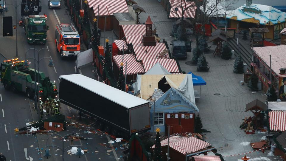 A truck is towed away as forensic experts examine the scene after a truck crashed into a Christmas market in Berlin.