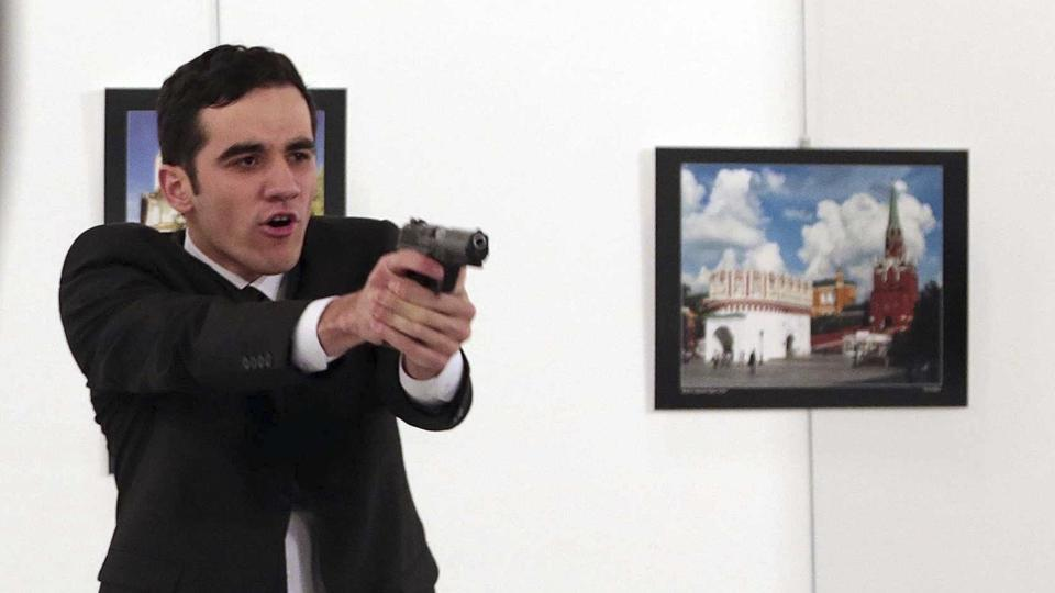 A gunman points his gun at those at an art gallery after shooting dead Russian ambassador to Turkey, Andrei Karlov, in Ankara, Turkey, on December 19, 2016.